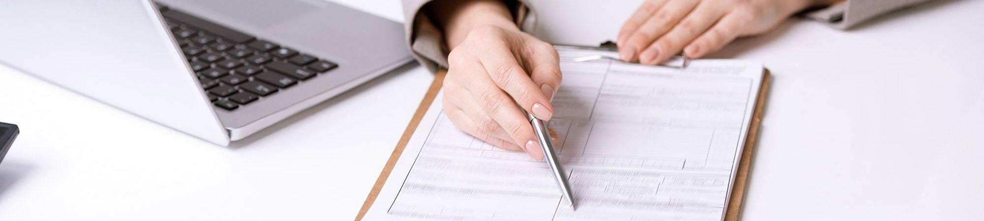 Policies Header Image - Woman with pen pointing to document